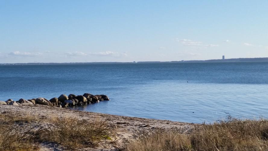 Von Sturm und Schnee gezeichnetes Dünenstück am Strand mit Blick auf klares, blaues Wasser udn einen leicht bedeckten Himmel und das schemenhaft zu erkennende gegenüberliegende Ufer.