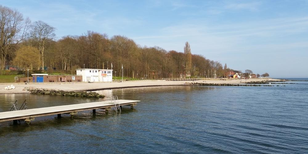 Panoramablick von der Wasserseite aus gesehen auf das Neustädter Strandbad mit grünenden Bäumen im Hintergrund an einem warmen, sonnigen Frühlingstag