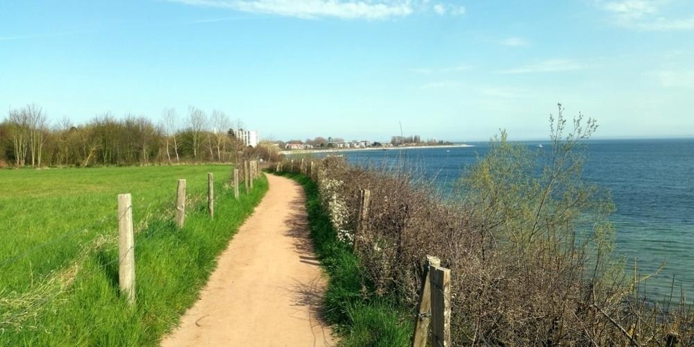 Sandwanderweg mit Strand und Promenade von Pelzerhaken in Sichtweite inmitten einer umrahmt einer grünen Wiese mit Wald auf der einen und der blauen Ostsee auf der anderen Seite